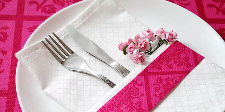 Weisse Stoffserviette mit rosa Bändchen